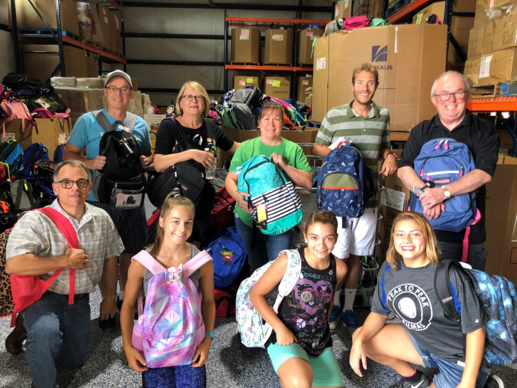 The team is all smiles after assembling backpacks for A Precious Child's Fill A Backpack drive